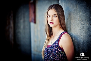High School Senior photographed in the Historic Flour Mill with metal cylinders as background.